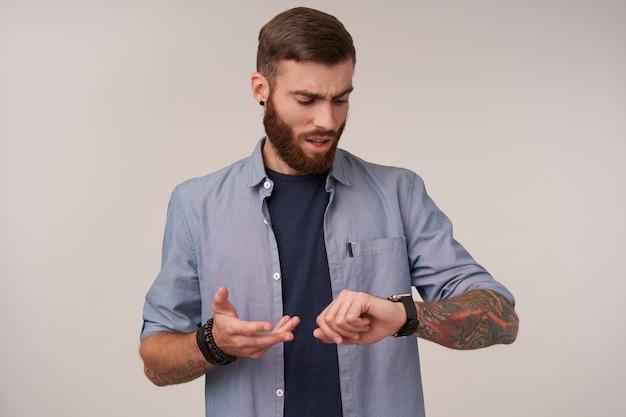 Niezadowolony młody brodaty mężczyzna z tatuażami w zwykłych ubraniach, patrząc na zegarek i zły, że ktoś, na kogo czeka, spóźnia się, pozuje na biało