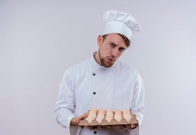 Niezadowolony młody brodaty szef kuchni w białym mundurze kuchennym i kapeluszu trzymający karton jajek, patrząc na białą ścianę
