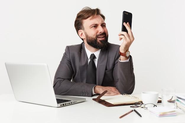 Niezadowolony młody brunet z brodą w modnej fryzurze i formalnym ubraniu podczas pracy w biurze z notatnikiem i laptopem, patrząc z dąsem na smartfonie w uniesionej dłoni