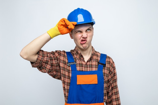 Niezadowolony młody budowniczy mężczyzna noszący mundur w rękawiczkach