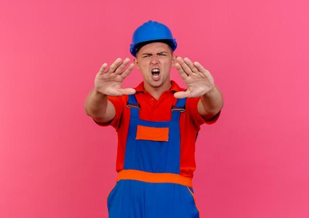 Niezadowolony młody budowniczy mężczyzna w mundurze i hełmie ochronnym pokazujący gest stopu na różowo