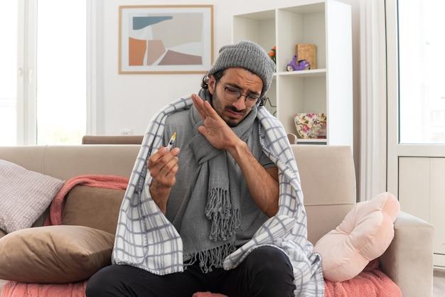 Niezadowolony młody chory mężczyzna w okularach optycznych owinięty w kratę z szalikiem na szyi w czapce zimowej trzymający i patrzący na strzykawkę siedzącą na kanapie w salonie