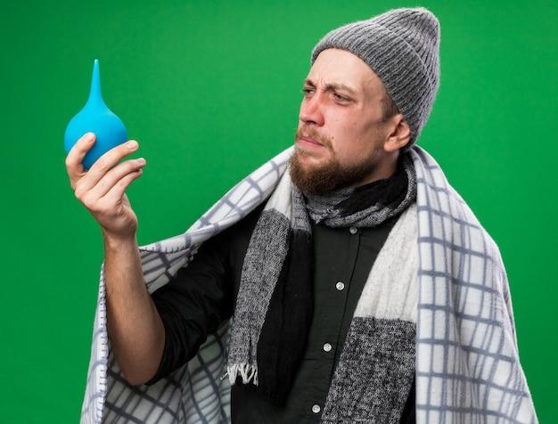 Niezadowolony młody chory słowiański mężczyzna z szalikiem na szyi owiniętym w kratę, ubrany w zimową czapkę, trzymający i patrzący na lewatywę odizolowaną na zielonej ścianie z kopią przestrzeni