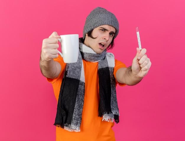 Niezadowolony młody chory w czapce zimowej z szalikiem, trzymając kubek herbaty z termometrem w aparacie na białym tle na różowym tle