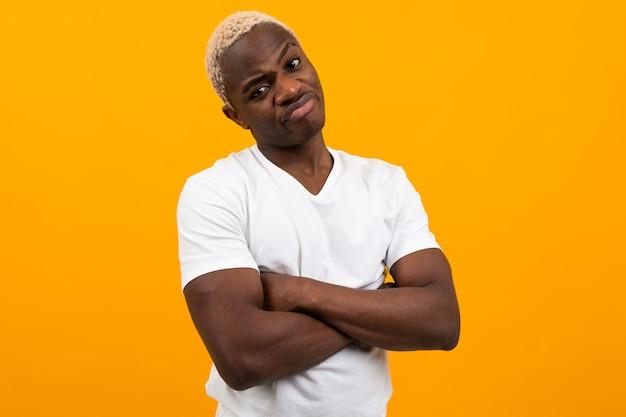 Niezadowolony młody czarnego afrykanina mężczyzna w białej koszulce pozuje na kolorze żółtym odizolowywającym z kopii przestrzenią