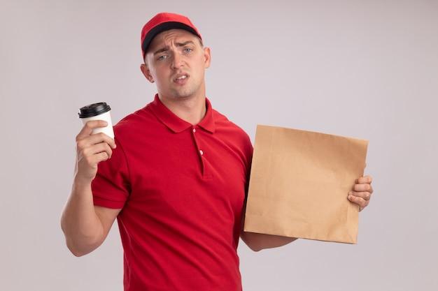 Niezadowolony młody człowiek dostawy ubrany w mundur z czapką, trzymając papierowy pakiet żywności z filiżanką kawy na białym tle na białej ścianie