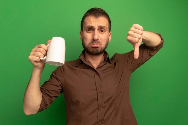 Niezadowolony młody człowiek patrząc z przodu trzymając kubek do góry nogami, pokazując kciuk w dół na białym tle na zielonej ścianie