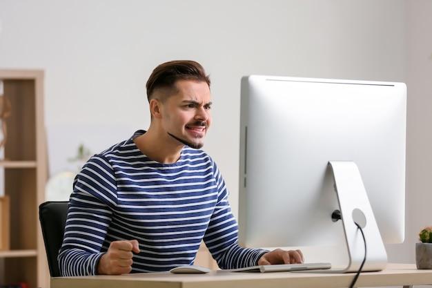 Niezadowolony młody człowiek po przegranej grze komputerowej w domu
