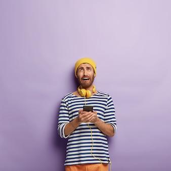 Niezadowolony młody człowiek trzyma nowoczesny smartfon, patrzy w górę z żałosnym wyrazem twarzy, nie może połączyć się z internetem
