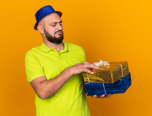 Niezadowolony młody człowiek w imprezowym kapeluszu, trzymający i patrzący na pudełka na prezenty na pomarańczowej ścianie
