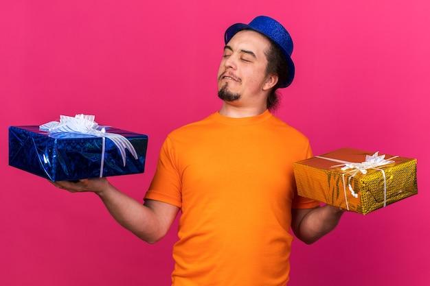 Niezadowolony młody człowiek w imprezowym kapeluszu, trzymający i patrzący na pudełka na prezenty na różowej ścianie