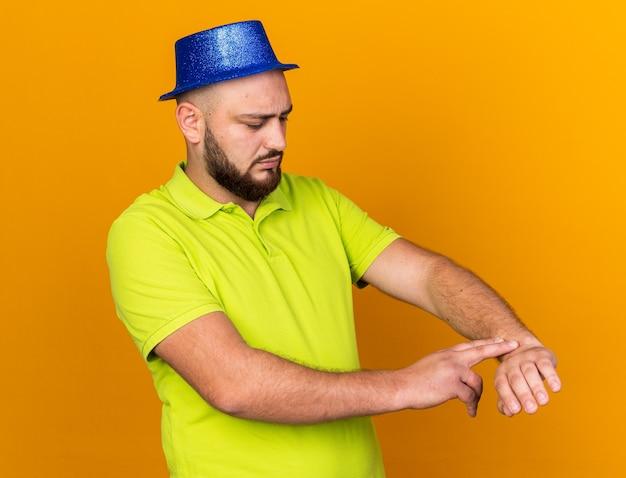 Niezadowolony młody człowiek w kapeluszu imprezowym pokazującym gest zegara na nadgarstku