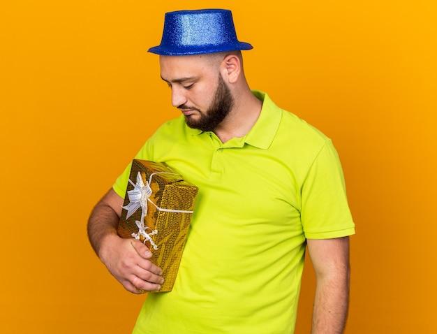 Niezadowolony młody człowiek w kapeluszu imprezowym, trzymający i patrzący na pudełko na prezent na pomarańczowej ścianie