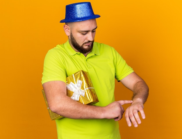Niezadowolony młody człowiek w kapeluszu imprezowym, trzymający pudełko pokazujące gest zegara na nadgarstku na pomarańczowej ścianie