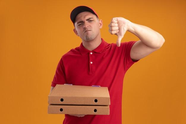 Niezadowolony młody dostawca ubrany w mundur z czapką trzymający pudełka po pizzy pokazujący kciuk w dół na pomarańczowej ścianie