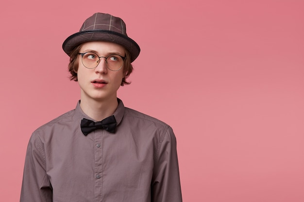 Niezadowolony młody, elegancko ubrany facet słucha nieuważnie moralizującego rodziców, odwraca się i patrzy w prawo na pustej przestrzeni kopii, na różowym tle