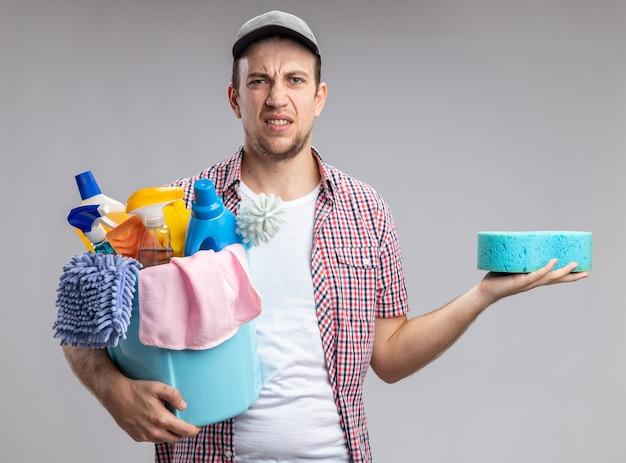 Niezadowolony młody facet sprzątający w czapce trzymającej wiadro z narzędziami do czyszczenia i gąbką do czyszczenia na białym tle