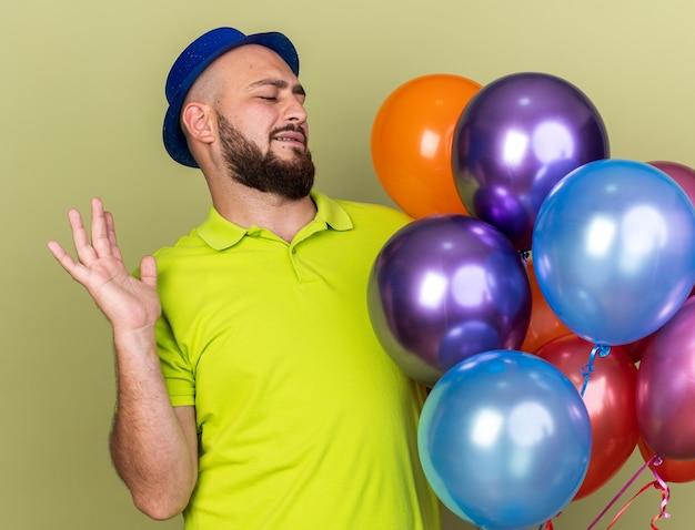 Niezadowolony młody facet w imprezowym kapeluszu, trzymający i patrzący na balony rozkładające rękę na oliwkowo-zielonej ścianie