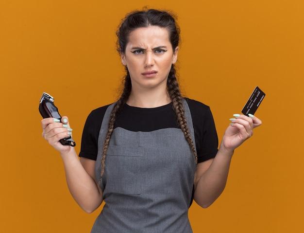 Niezadowolony młody fryzjer żeński w mundurze trzymający kartę kredytową i maszynki do strzyżenia włosów odizolowanych na pomarańczowej ścianie
