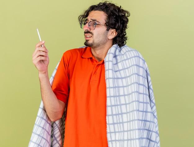 Niezadowolony młody kaukaski chory mężczyzna w okularach zawinięty w kratę, trzymając i patrząc na termometr na oliwkowej ścianie