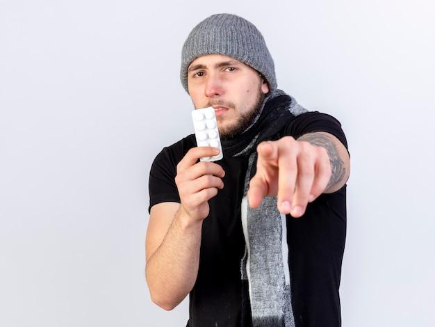 Niezadowolony młody kaukaski chory w czapce zimowej i szaliku trzyma paczkę tabletek medycznych, wskazując na białej ścianie z miejscem na kopię