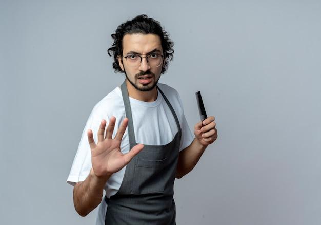 Niezadowolony młody kaukaski fryzjer męski w okularach i falującej opasce do włosów w mundurze trzymając grzebień i wyciągający rękę w aparacie gestykuluje zatrzymaj się na białym tle z miejscem na kopię