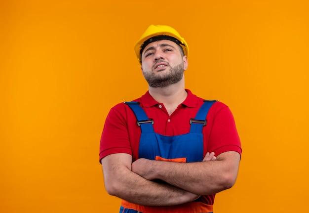 Niezadowolony młody konstruktor w mundurze konstrukcyjnym i kasku ze skrzyżowanymi rękami na piersi