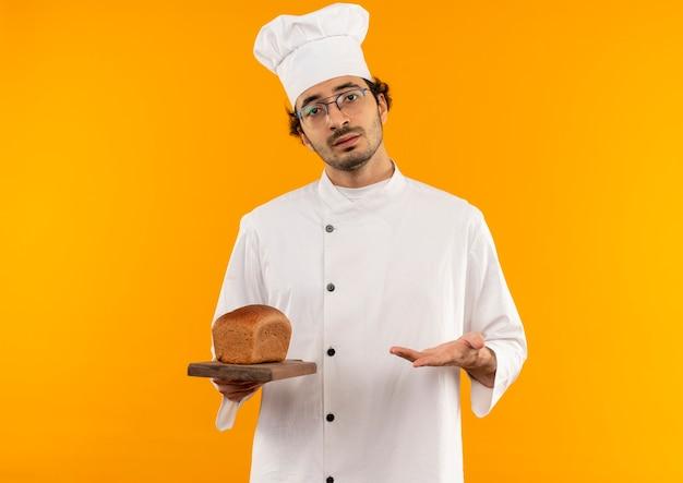 Niezadowolony młody kucharz mężczyzna w mundurze szefa kuchni i okularach trzyma i wskazuje ręką na brodę na desce do krojenia na białym tle na żółtej ścianie