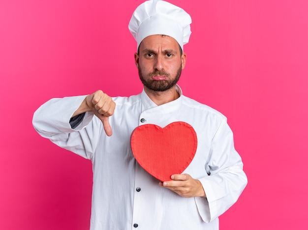 Niezadowolony młody kucharz rasy kaukaskiej w mundurze szefa kuchni i czapce trzymającej kształt serca pokazujący kciuk w dół