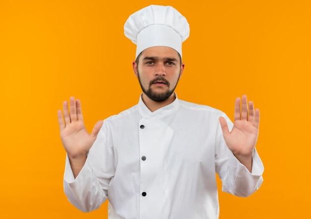 Niezadowolony młody kucharz w mundurze szefa kuchni pokazuje puste ręce na pomarańczowej przestrzeni