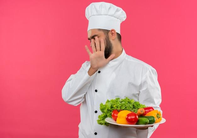 Niezadowolony młody kucharz w mundurze szefa kuchni, trzymając talerz warzyw i gestykulujący nie na różowej przestrzeni