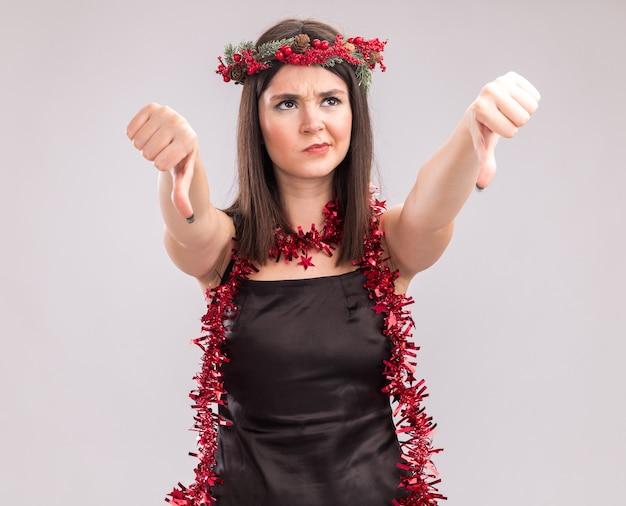 Niezadowolony młody ładny kaukaski dziewczyna nosi świąteczny wieniec głowy i blichtr girlanda wokół szyi patrząc w górę pokazując kciuk w dół na białym tle na białym tle