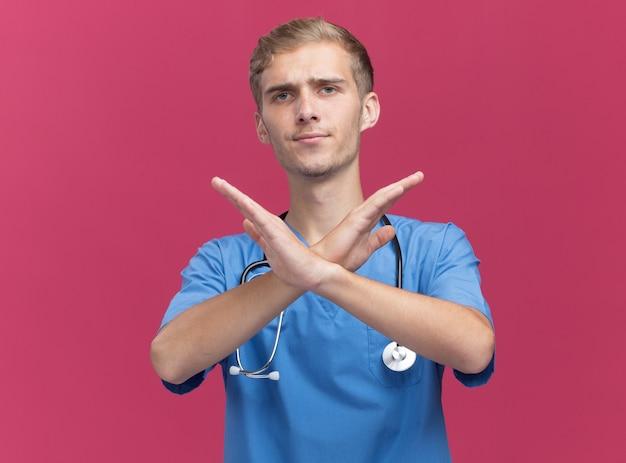 Niezadowolony młody lekarz mężczyzna ubrany w mundur lekarza ze stetoskopem pokazujący gest nr na różowej ścianie