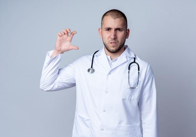 Niezadowolony młody lekarz płci męskiej ubrany w szlafrok i stetoskop na szyi, pokazujący rozmiar na białym tle