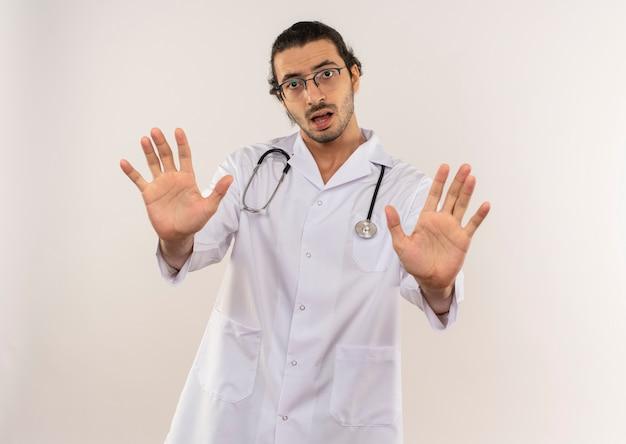Niezadowolony młody lekarz płci męskiej z okularami optycznymi, ubrany w białą szatę ze stetoskopem, pokazujący gest zatrzymania na odosobnionej białej ścianie z miejscem na kopię