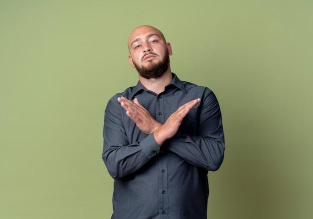 Niezadowolony młody łysy mężczyzna call center nie robi żadnego gestu w aparacie na białym tle oliwkowej zieleni z miejsca na kopię