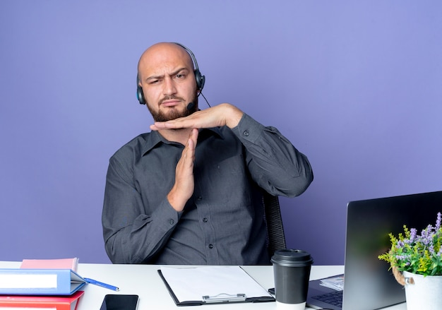 Niezadowolony młody łysy mężczyzna call center sobie zestaw słuchawkowy siedzi przy biurku z narzędzi pracy robi gest limitu czasu na białym tle na fioletowym tle