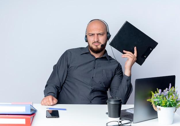 Niezadowolony młody łysy mężczyzna call center sobie zestaw słuchawkowy siedzi przy biurku z narzędzi pracy trzymając schowek na białym tle