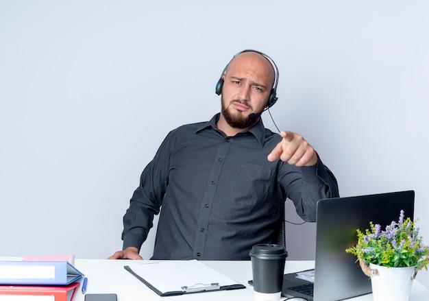 Niezadowolony młody łysy mężczyzna call center sobie zestaw słuchawkowy siedzi przy biurku z narzędzi pracy, wskazując na aparat na białym tle