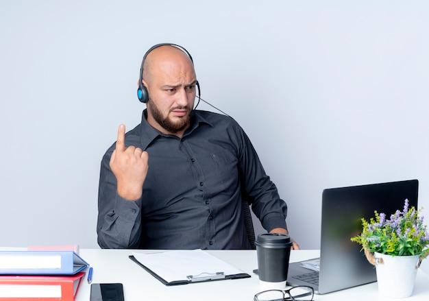 Niezadowolony młody łysy mężczyzna call center sobie zestaw słuchawkowy siedzi przy biurku z narzędziami pracy podnosząc palec i patrząc na laptopa na białym tle
