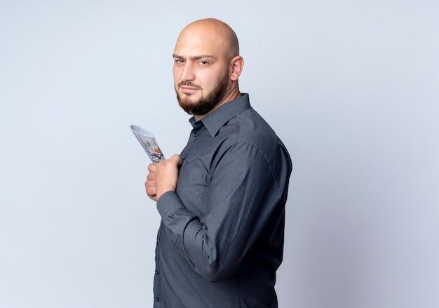 Niezadowolony młody łysy mężczyzna call center stojący w widoku profilu trzymając pieniądze na białym tle na białym tle z miejsca na kopię