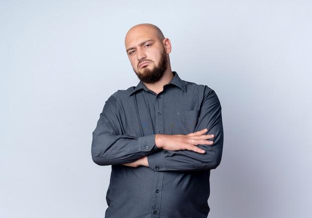 Niezadowolony młody łysy mężczyzna call center stojący z zamkniętą posturą na białym tle na białym tle z miejsca na kopię