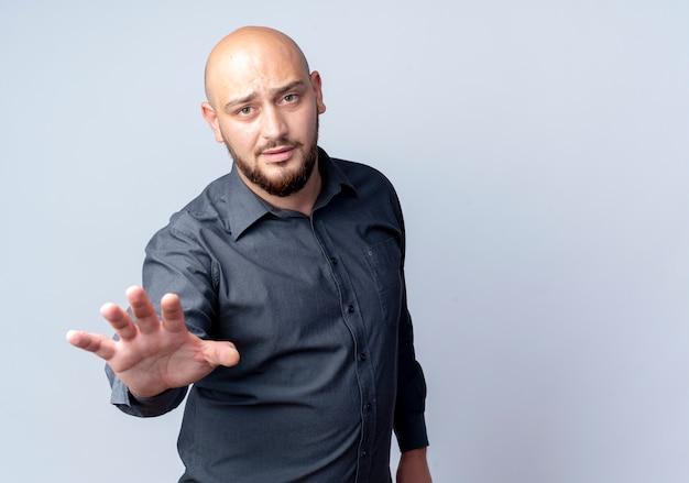 Niezadowolony młody łysy mężczyzna call center wyciągając rękę w kierunku kamery na białym tle na białym tle z miejsca na kopię