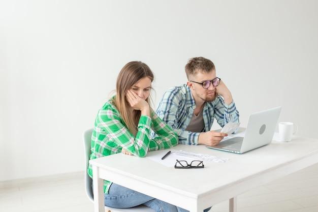 Niezadowolony młody mąż i żona przeliczają rachunki za media na opłacenie mieszkania i piszą