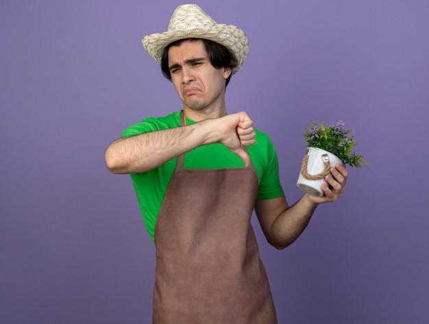 Niezadowolony młody męski ogrodnik w mundurze w kapeluszu ogrodniczym trzymający kwiat w doniczce pokazujący kciuk w dół