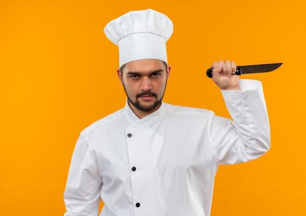 Niezadowolony młody mężczyzna kucharz w mundurze szefa kuchni trzymając nóż na białym tle na pomarańczowej przestrzeni