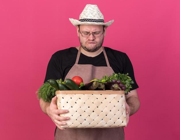 Niezadowolony młody mężczyzna ogrodnik w kapeluszu ogrodniczym, trzymający i patrzący na kosz warzyw na białym tle na różowej ścianie