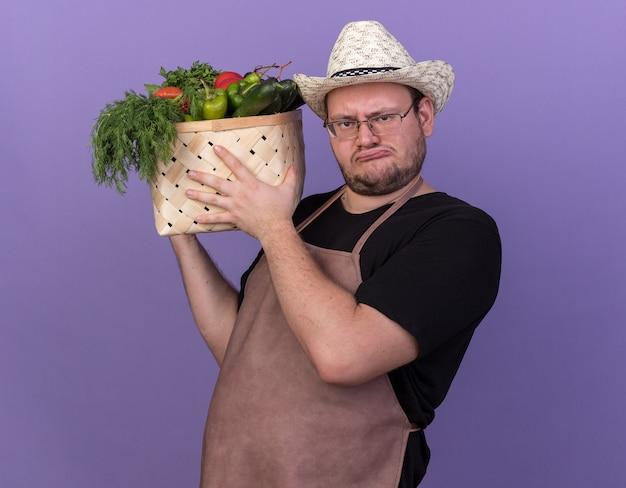 Niezadowolony młody mężczyzna ogrodnik w kapeluszu ogrodniczym trzymający kosz warzyw na białym tle na niebieskiej ścianie