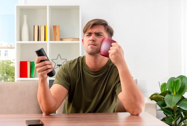 Niezadowolony młody przystojny blondyn siedzi przy stole trzymając pilota od telewizora i kładąc kubek w twarz
