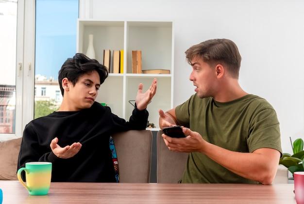 Niezadowolony młody przystojny blondyn trzyma i wskazuje na telefon ręką siedzącą przy stole i patrząc na nieświadomego młodego przystojnego chłopca brunetki